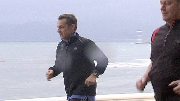 Sarkozy jogs in the rain as clouds gather over Europe