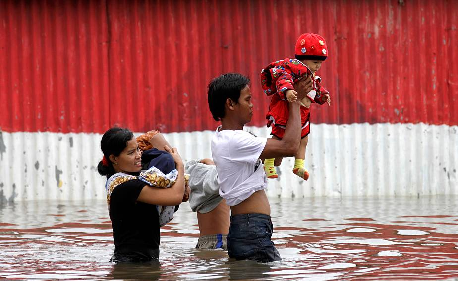 A man carrying his baby walks through flood waters