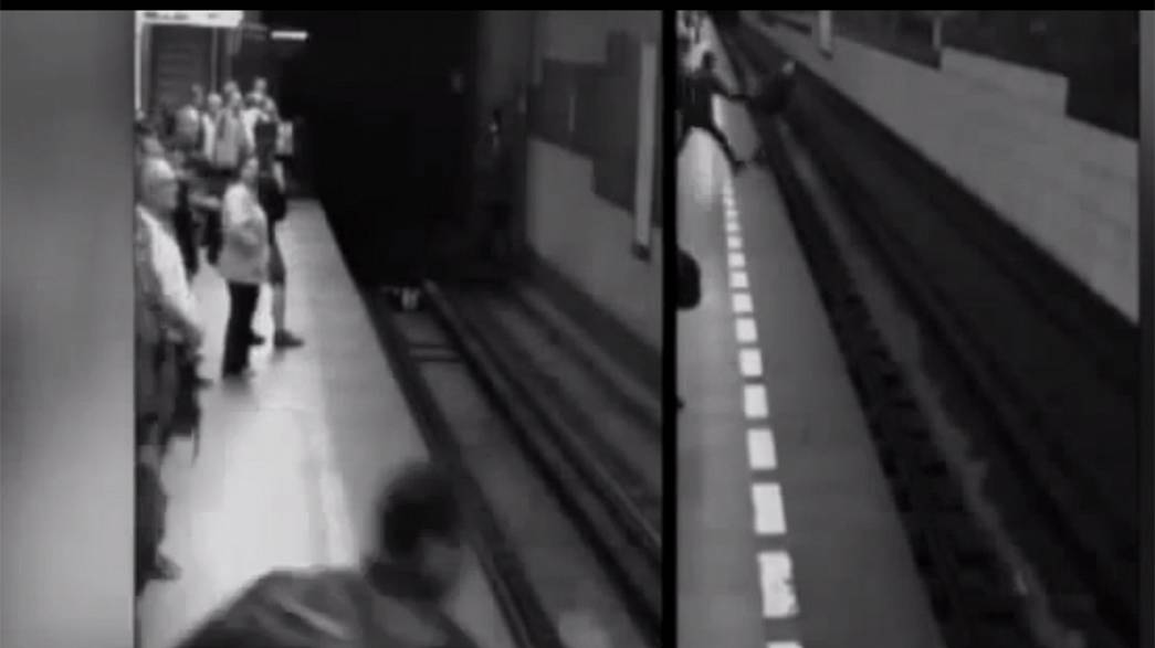A woman 'walks off' after falling under train - Video