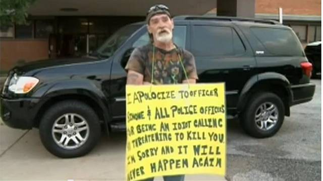 Man who threatened police made to stand with sign calling himself an idiot