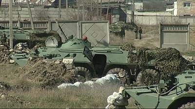 Ukrainian troops eye their Russian counterparts across the border with suspicion