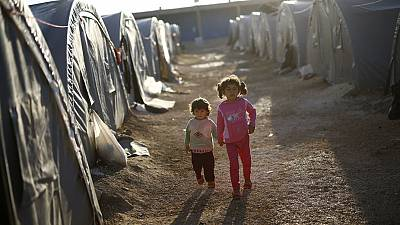 Kurdish refugees hand-in-hand in refugee camp
