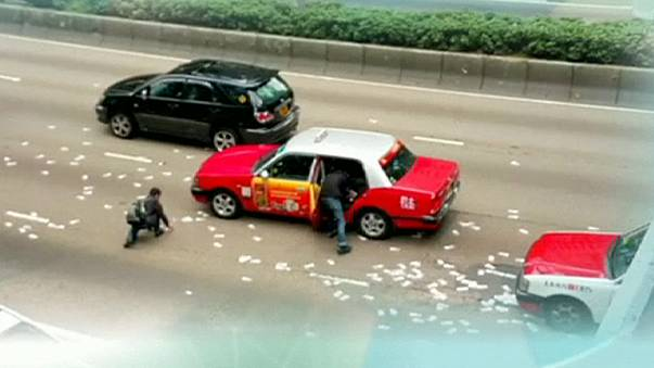 Rush for money after security van spills banknotes on Hong Kong road