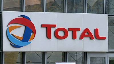 Total cuts investment and employees to counter weaker oil prices