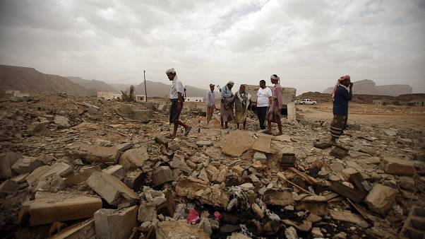 Image: Tribesmen stand on the rubble of a building destroyed by a U.S. dron