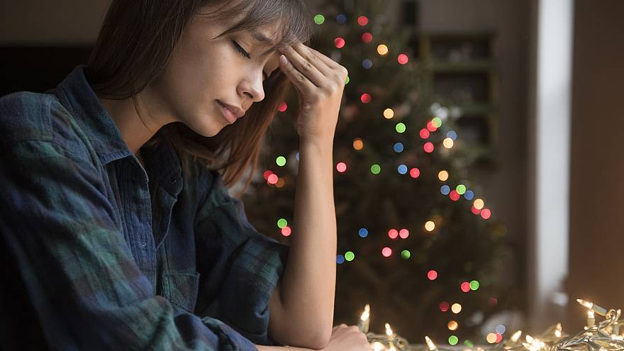 Image: A woman sits by a Christmas tree