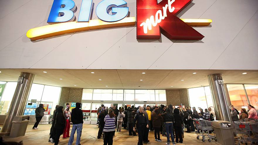 Image: Shoppers wait outside a Kmart in Griffith