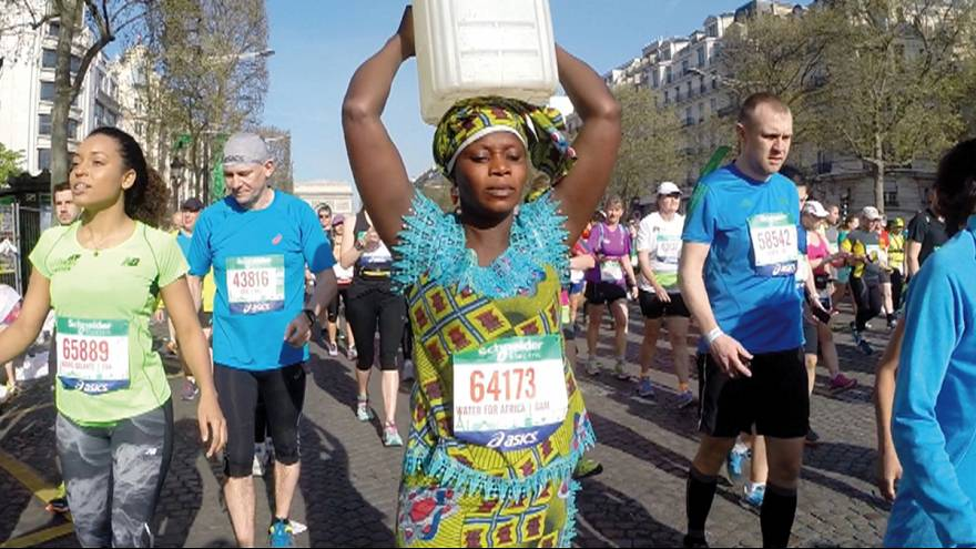 Woman carries can of water on her head along Paris marathon