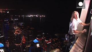 French 'spiderman' reaches new heights scaling world's tallest twisted building in Dubai