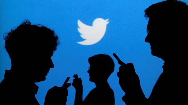 Image: People holds mobile phones in front of a Twitter logo in an illustra