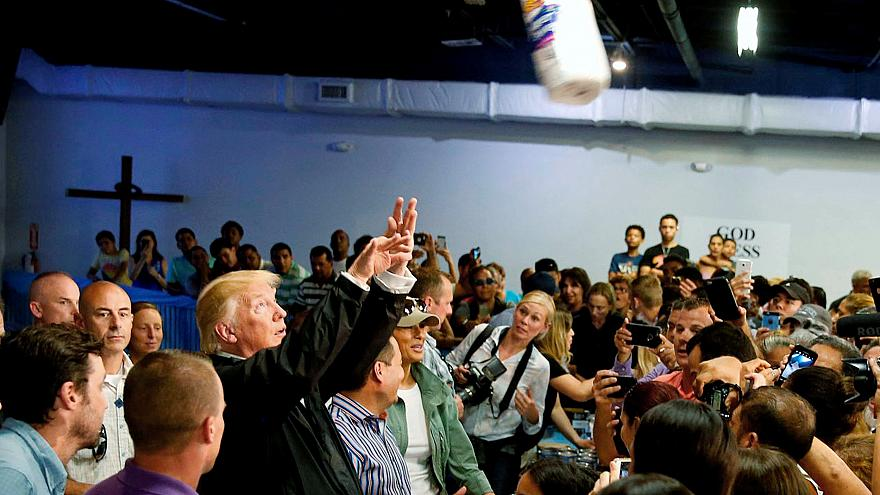 Image: President Trump throws a roll of paper towels to residents gathered
