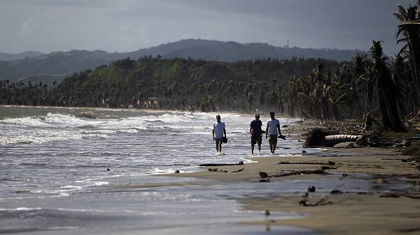 Image: Tourists wade in the water along the beach in the Punta Santiago bea