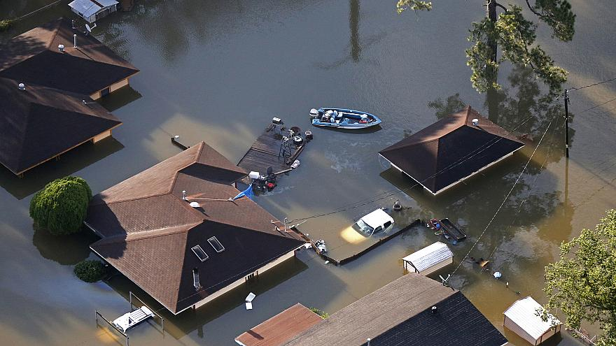Image: A boat sits near flooded homes in the aftermath of Tropical Storm Ha