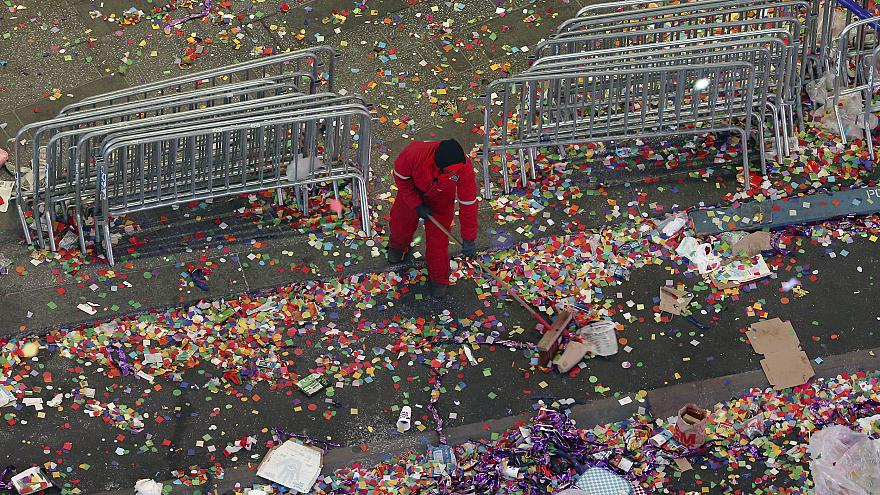 Image: A member of the cleanup crew sweeps confetti in New York's Times Squ