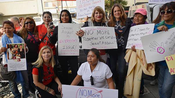 """Comedian Tess Rafferty, back row in red shirt, television reporter Lauren Sivan, front row in red shirt, and movie producer Cathy Schulman, third from right, pose with members of Alianza Nacional at the """"Take Back The Workplace"""" event on Nov. 12 in Hollyw"""