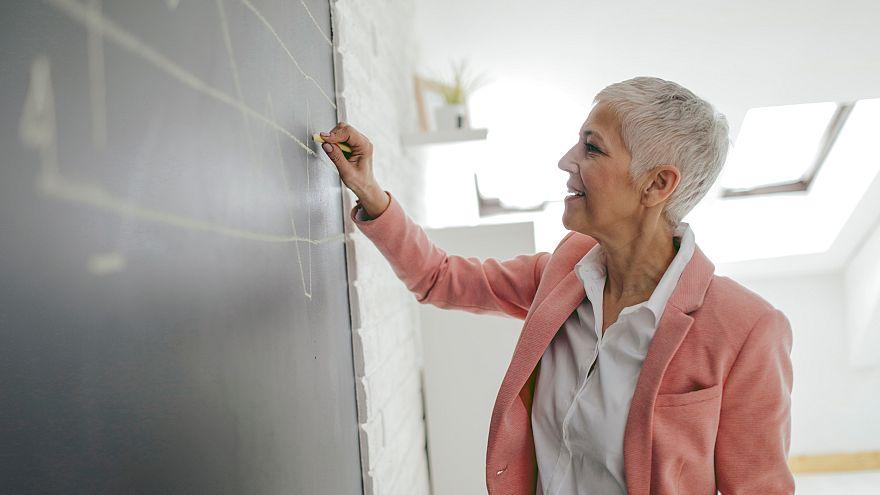 Businesswoman Drawing Chart On Blackboard In Her Office.