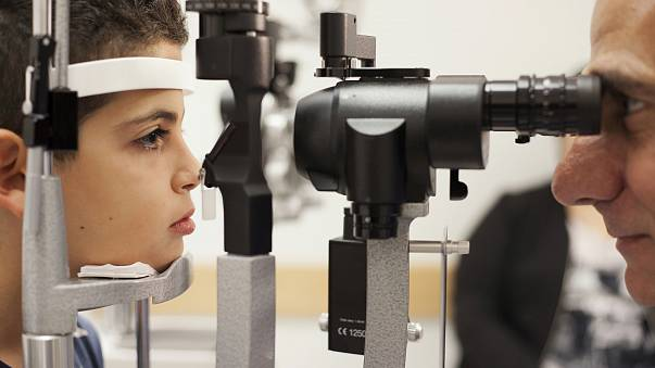 Image: A doctor checks the eyes of a patient who received a blindess gene t