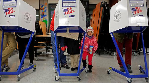 Image: Myla Gibson, 3, waits as her father Ken Gibson fills out a ballot fo