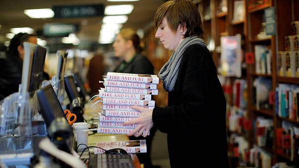 """Image: An employee holds copies of the book """"Fire and Fury: Inside the Trum"""