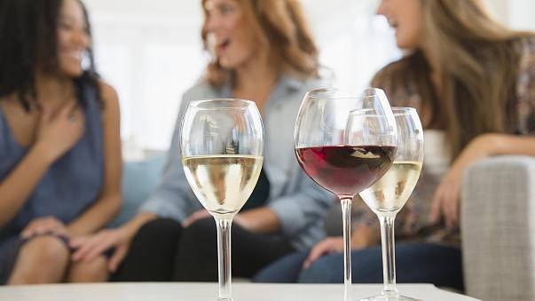 Image: Women drinking wine and talking on sofa in living room