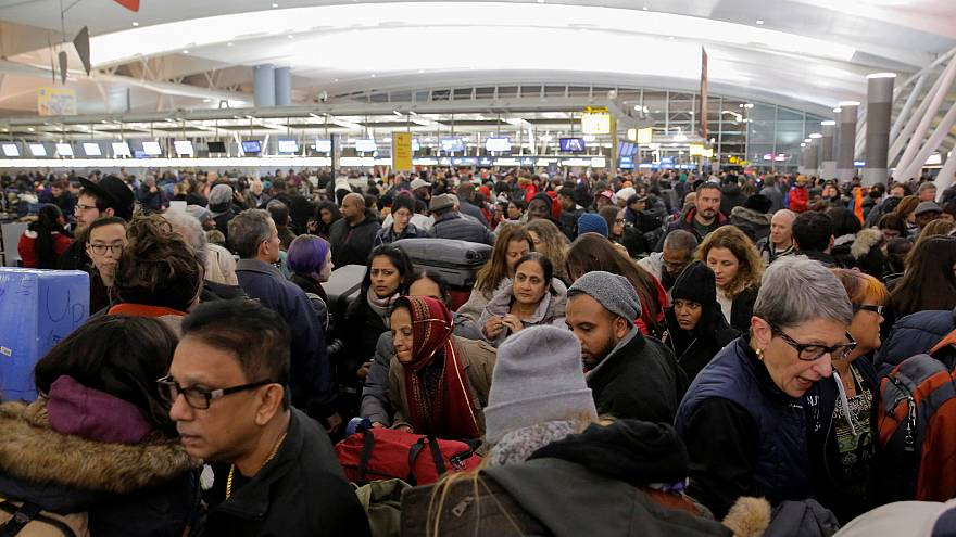 Image: Large crowds try to make their way through the departures area of Te
