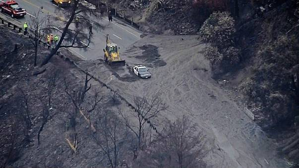 A police car is surrounded by a mudslide in the La Tuna fire burn area in Southern California.