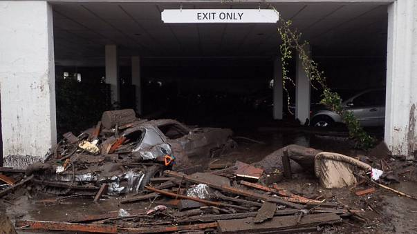 Vehicles carried by the mud flow sit at the exit of the parking garage to the Montecito Inn.