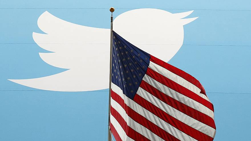 Image: The Twitter Inc. logo is shown with the U.S. flag during the company