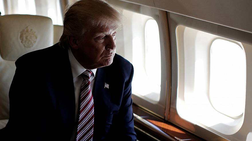 Image: Trump looks out the window as he travels aboard his plane between ca