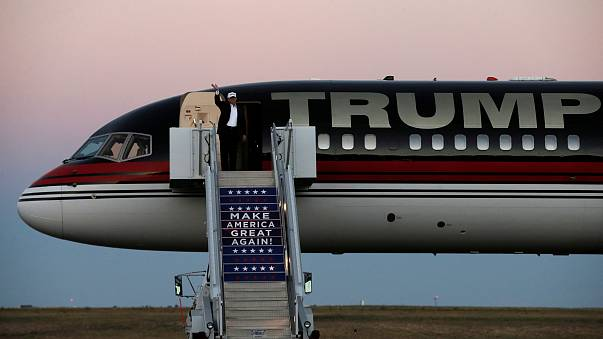 Image: Trump waves as he walks off his plane at a campaign rally in Colorad