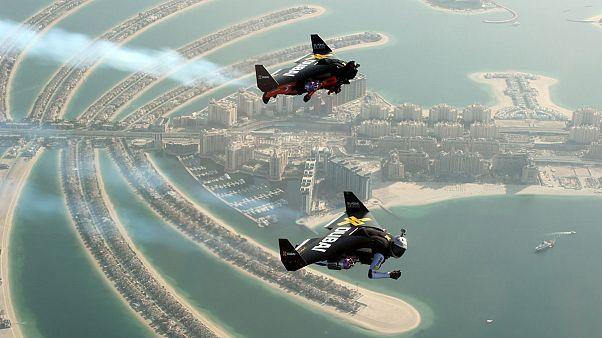 بالفيديو: رجلان يطيران بأجنحة فوق جزيرة النخلة بدبي