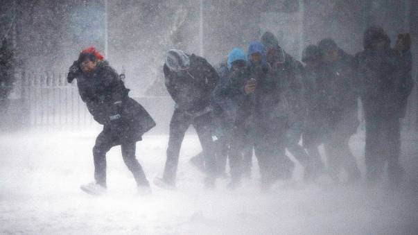 Image: People struggle to walk in the blowing snow during a winter storm
