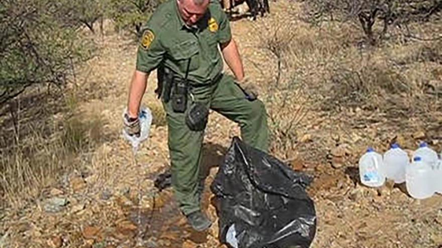 Image: A Border Patrol agent empties a water bottle