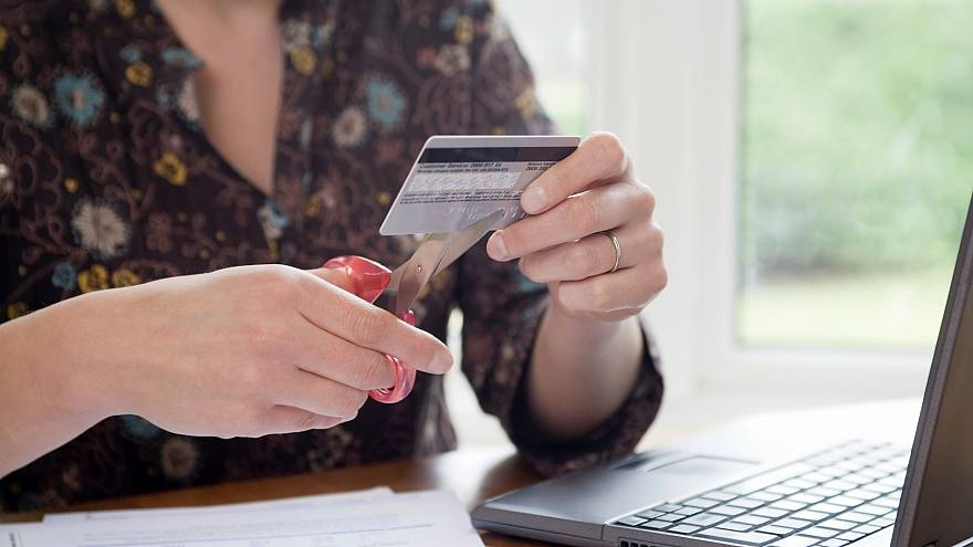 Image: Woman Cutting Credit Card with Scissors