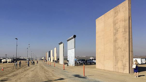 Image: People look at prototypes of a border wall
