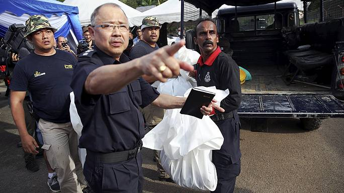 Malaysian forensic officers examine remains of migrants found along Thai border