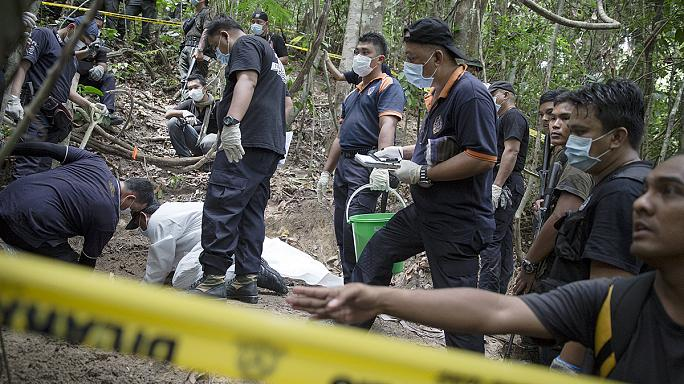 Forensic police in Malaysia exhume migrant corpses buried along the Thai border