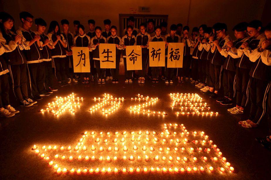 Des étudiants chinois prient pour les victimes de la catastrophe du ferry