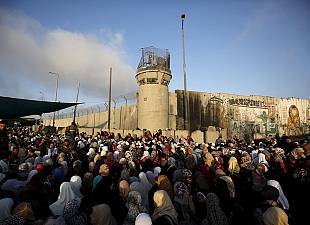 Palestinians wait to cross the border to pray