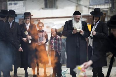 Ultra-Orthodox men pray and burn leavened bread in Jerusalem\'s Mea Shearim neighborhood.