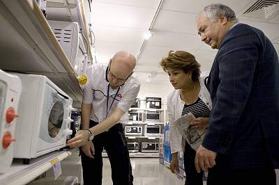 A salesman demonstrates a microwave oven to customers at a Conforama store in Paris.