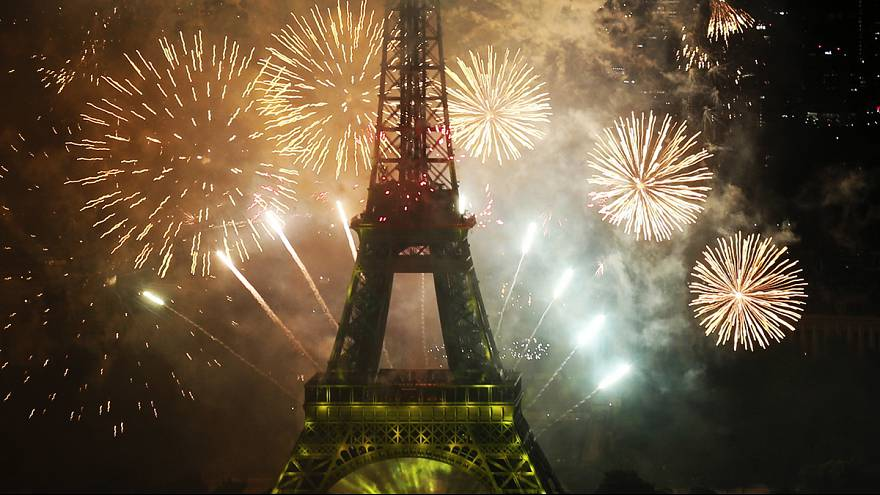 Eiffel Tower lit up by fireworks for Bastille Day