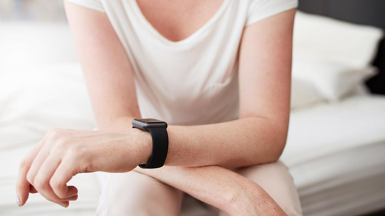 Cropped shot of a woman sitting on bed wearing a smart watch