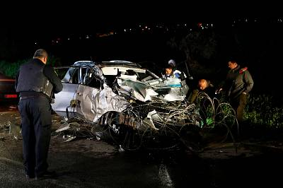Israeli security forces and forensics inspect the destroyed vehicle that was used by a Palestinian assailant in a car ramming attack targeting a group of Israeli soldiers near Mevo Dotan in the north of the occupied West Bank on March 16, 2018.