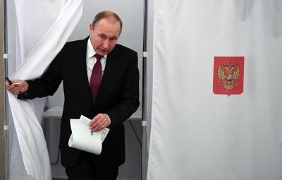 President Vladimir Putin walks out of a voting booth at a polling station during Russia\'s presidential election in Moscow on March 18, 2018.