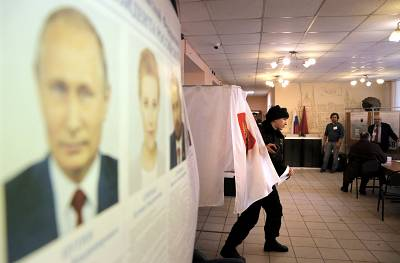 Portraits of the presidential candidates are presented while voters prepare to cast their ballots  at a polling station in Moscow, Russia, 18 March 2018.