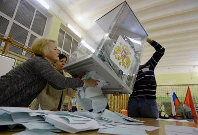 Members of a local election commission empty a ballot box as they start counting votes during Russia\'s presidential election in Saint Petersburg on March 18, 2018.