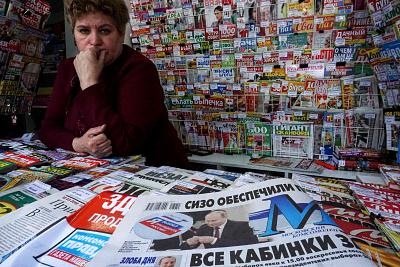 Newspapers show Vladimir Putin after his reelection at a newsstand in Moscow on Monday.