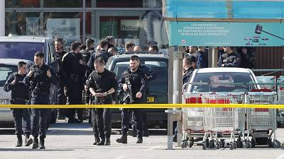 Armed gendarmes stand outside the Super U after their assault Friday on the supermarket where a gunman took hostages in Trebes, southern France.