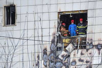 Officials at the scene of the shopping mall fire on Tuesday.